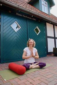 Vor der grünen Eingangstür des Hüder Dorfhauses sitzt Yogalehrerin Dagmar Buck im Lotussitz. Ihre Hände hat sie vor der Brust zum Namasté-Gruß erhoben.