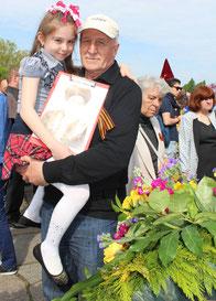 Großvater mit Enkeltochter auf dem Arm, in der Hand das Bild des gefallenen Ur-Opas aus Usbekistan, 9.Mai 2015 Sowjet. Ehrenmal Treptow. Foto: Helga Karl
