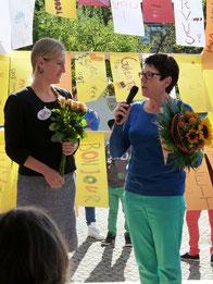 Frau Haug begrüßt Frau Vogt mit einem Blumengruß an der GMS Ergenzingen