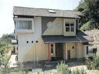 高台の丸窓のある家