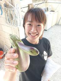 まるで天狗のような形のナスを持つ緑川さん=23日、竹富島