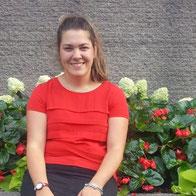 Femme souriante aux cheveux châtains attachés à l'arrière portant un chandail rouge.