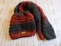 grau rote Mütze und grau roter Schal auf Holzboden