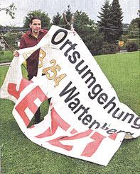 Jan Krieger zeigt das im Sommer von Unbekannten zerschnittene Plakat der Bürgerinitiative. Sie setzt sich für den Bau der Ortsumgehung ein.