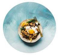 Teller mit Nudeln, Spiegelei und Zitrone auf blauem Hintergrund