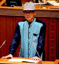 議案説明をする翁長知事。議場内での帽子着用は新里議長が許可した=12日、県議会