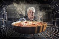 Eine Dame welche einen fertigen Kuchen aus dem Backofen holt.