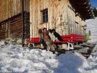 Frau mit vier Hunde vor Hütte in Lech, Arlberg