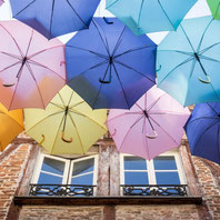 Photo of a window of a half-timbered building with a work of art street art of multicolored umbrellas in France taken by Marie Deschene photographer for Pakolla
