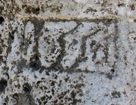 Die freigelegte Datierung der Tuffsteinsäule weist vermutlich auf das Jahr 1556 hin.