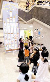 作った「100階建ての家」を吊り上げる子どもたち=5日午前、市立図書館