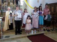 Pfarrer Raimund Arnold (l.) mit den Täuflingen und deren Angehörigen
