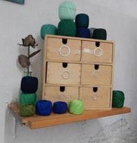 Holzbox für Knopfrohlinge und grüne und blaue Garnknäuel