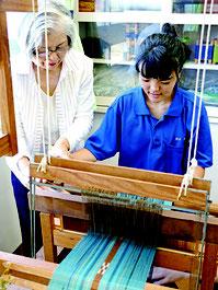 大浜さんからミンサー織りの指導を受ける生徒=17日午前、八特支