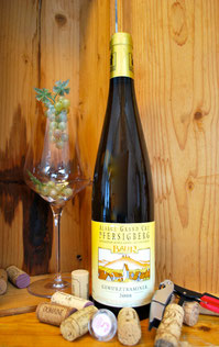 Een fles Gewurztraminer Grand Cru Pfersichsberg in een kist met een wijnglas