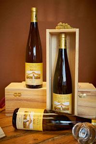 Drie flessen Elzas Riesling Grand Cru Brandt, staand en liggend op tafel en in een kist