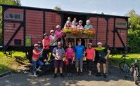 Die Teilnehmer der Radltour vor einem  historischen Güterwaggon.