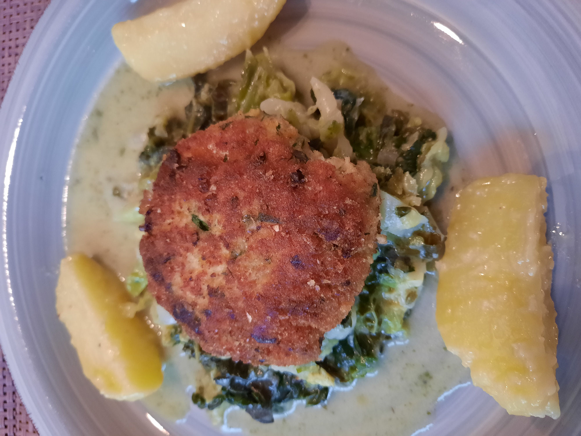 Hirse-Fisch-Laibchen auf Wirsinggemüse und Buttererdäpfeln