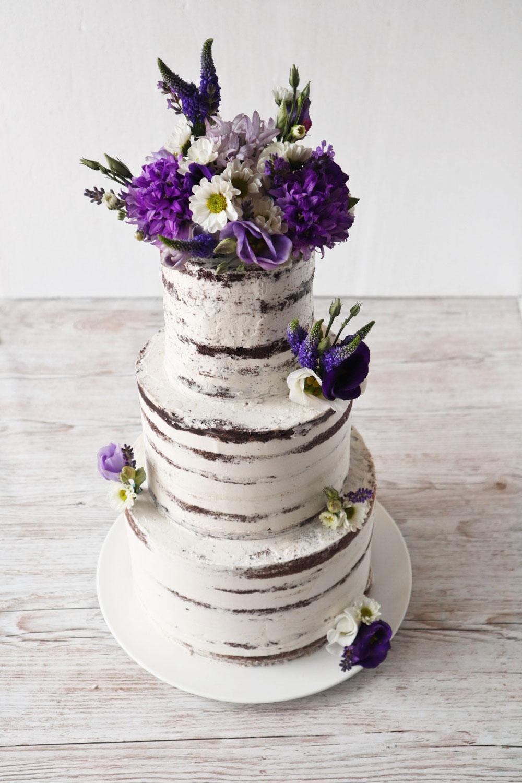 Hochzeitstorte mit lila Blumen