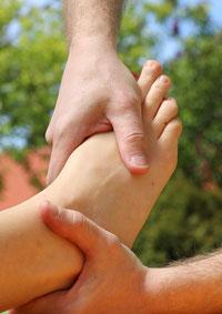 Die linke Hand von Patrick Schnerr aus Aalen hält einen Fuß, während die rechte Hand mit dem Daumen den Fußrücken eines Gastes massiert.