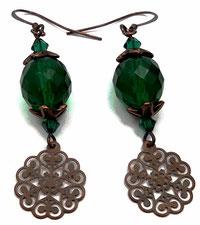 photo de boucles d'oreilles en métal cuivré avec perles en verre vert émeraude facettées et estampes rosaces en breloques pendantes