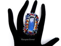 photo d'une bague brodée de créateur en cristal rouge avec anneau en argent portée sur la main