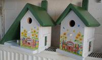 Nestkastje wit met bloemen en groen dak, welkom vogels vogelhuisje