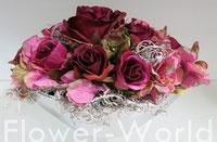 Gestecke, Tischaufleger, Kränze und Wandschmuck, stellen unsere Floristen in anmutiger Farbkombination, im Deko-Store her. Hier: Rosengesteck in ovalem, silbernen Porzellan-Gefäß, bordeaux-malve.