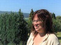 Lebensfreude-Trainerin Ria Kestel im Sonnenschein vor Gebirge mit Nadelwald