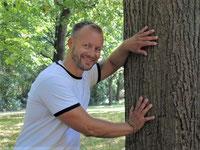Personal Trainer Dennis Zimmer lehnt sich gegen einen Baum und ertastet mit beiden Händen den Stamm