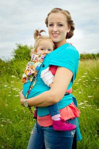 Der Huckepack Wrap Tai ist eine Babytrage, bei der die Träger über den Schultern aufgefächert werden können.Der Hüftgurt wird mit einer Schnalle geschlossen.