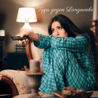 Gelangweilte Frau im Pyjama und Fernbedienung in der Hand, Wohnzimmer