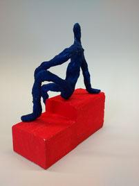 Sitzende Figur auf rotem Sockel im Stil von Alberto Giacometti.