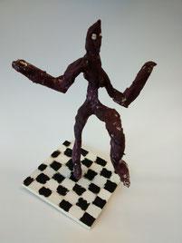 Stehende Figur auf Schachbrettmuster im Stil von Alberto Giacometti.