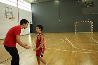 Javi, entrenador del Pre-mini, parlant amb un dels seus jugadors durant el seu partit a casa.