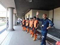 午後3時帰宅する北茨城特別支援学校の児童たちが乗ったバスをサッカー部の生徒が見送っている様子。