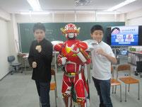ご当地ヒーローのスギヨ仮面と生徒たちが記念写真。