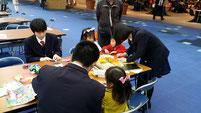 幼児と一緒に折り紙を折って遊ぶ生徒たち。