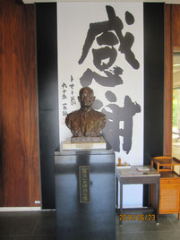 カゴメの創業者の像と、会社が何よりも大切にしている理念が書かれた掛け軸。