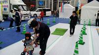 幼児に三輪車の安全運転を指導する生徒たち。