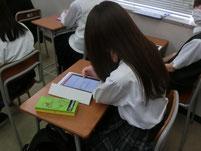 タブレット端末に授業の感想を入力する生徒