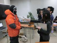 生徒が防寒具を着たままテレビ局のインタビュー