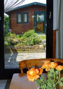 Blick aus der Küche auf die Terrasse und Gartenhaus