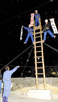 先輩団員の指導で、懸垂幕を掲示する(右から)三輪千夏さん、登野盛雅美さん、生駒さつきさん=7日午後8時半過ぎ、市消防本部