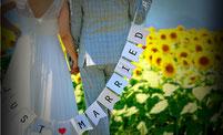 ひまわり畑でガーランドを持つ後ろ姿の新郎新婦様の結婚写真