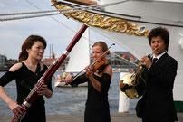 Musiker vor einem Schiff