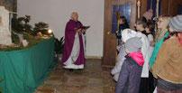 """Die """"Statio"""" mit Pfarrer Arnold vor der Adventskrippe."""