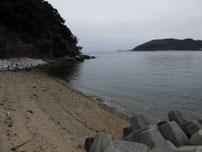 小田漁港 左側の波止 横の砂浜 の写真
