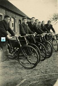 Zeven jongens met een fiets voor een oude boerderij.