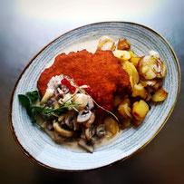 Bratkartoffeln, Schnitzel und Champignonrahmsoße auf ovalem Teller